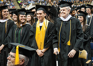 "Ninety-year-old John Downs (standing in front row, far right) celebrates his Bachelor of Arts degree, which he received after the whims of fate postponed the moment for more than 60 years. He attended Pitt's commencement with his large and loving family in the audience. Afterwards, he quipped:  ""It's nice to be out of college!"""