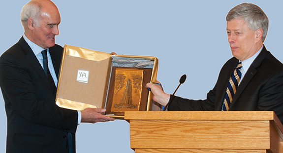 Ambassador Vale de Almeida accepts a gift of a craftsman's depiction of the Cathedral of Learning from Pitt Chancellor Mark A. Nordenberg.