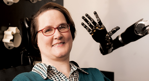 A brain-computer interface has enabled Jan Scheuermann, who has quadriplegia, to control a robotic arm with her mind.