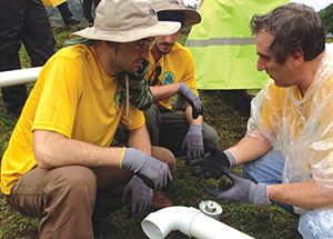 Pitt engineering students Gordon Louderback (left) and Ed Doyle (center) listen as Pitt Engineering Professor Daniel Budny (right) explains how to attach fittings to the end of a PVC pipe. Pitt students were installing the pipes to bring a reliable source of water to residents of Kuna Nega, Panama.