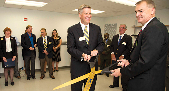 Pitt and Lubrizol Corp. officials participated in an Aug. 12 ribbon-cutting ceremony at the new Lubrizol Innovation Lab in Benedum Hall. In the background are Provost and Senior Vice Chancellor Patricia E. Beeson, on far left, and Gerald D. Holder, U.S. Steel Dean of Engineering, on far right. Holding the scissors, from left, are Pitt Chancellor Patrick Gallagher and Michael Vaughn, Lubrizol's corporate vice president of operations.