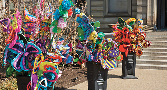 Recent snow flurries have made it easy to forget that it really is April. But the colorful Pop des Fleurs in front of the steps of Oakland's Carnegie Library serve as a promise of warmer days ahead. Made from colorful acrylic yarn, the flowers grew out of an idea conceived by a Fiberarts Guild of Pittsburgh member during the cold and dreary Pittsburgh winter of 2013-14. Soon, blasts of color appeared in front of the Carnegie Library. Pop des Fleurs then became a Community Outreach Project of the guild's Fiberart International 2016 being held in Pittsburgh. The project has several partners—including Pitt—who have made and placed displays at 16 other locations around the city. (Photo by Emily O'Donnell)