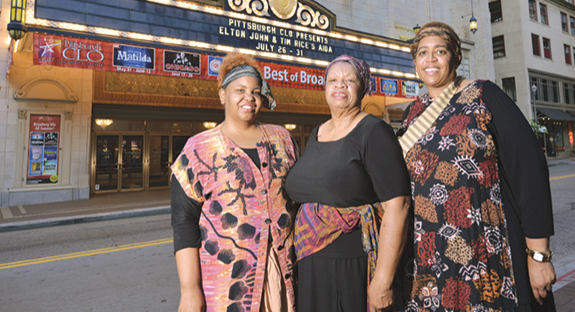 Two University staffers and an alumnus performed in the Pittsburgh Civic Light Opera's Aida at the Benedum Center, Downtown, July 26-31. Standing in front of the show's marquee are, from left, Tiffany Robinson, a teacher with Pitt's Child Development Center; Gwen Watkins (CGS '15), the former community activities coordinator for Pitt's Office of Community and Governmental Relations; and Michelle Denson-Laster, an administrative specialist in the Office of University Communications. The women are members of the Rodman Street Missionary Baptist Church, East Liberty. The CLO invited the church's choir members to perform nightly in one of the musical's scenes. (Photo by Nate Guidry)