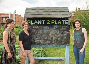 Pitt's Plant to Plate student organization manages an urban garden at the corner of Oakland Avenue and Sennott Street in Oakland. The garden's vegetables and fruits are donated to local food pantries. From left, Erika Ninos, sustainability program coordinator, Office of PittServes; Holly Giovengo (A&S '15), who was a student leader in sustainability initiatives on campus while an undergraduate and an AmeriCorps VISTA volunteer last year; and Alyssa Martinec, the student sustainability intern for Pitt's Department of Housing who is active in Pitt's Take Back the Tap initiative. (Photo by Emily O'Donnell)