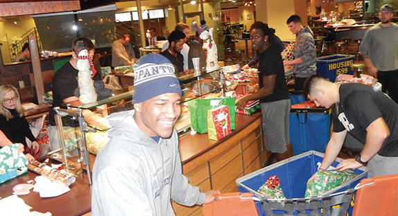 The entire Pitt football team, led by Head Coach Pat Narduzzi, wrapped presents, stuffed gift bags, and sorted packages on Dec. 22 in preparation for the 2015 Christmas Day at Pitt. The free and annual event, held in Litchfield Towers' Market Central dining space, served more than 2,400 meals to members of the Pittsburgh community in need. Pitt partnered with campus food-services provider Sodexo and the Salvation Army—as well as more than 225 volunteers from Pitt. An additional 134 student athletes volunteered prior to the event, including members of the University's men and women's basketball teams, as well as football, swimming and diving, and gymnastics teams.