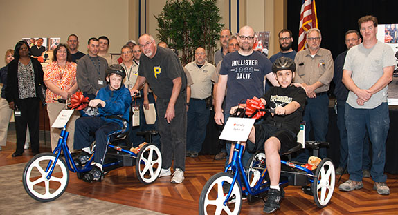 "Pitt employees contributed about $5,400 to buy three adaptive bicycles for local children with special needs. Contributing staffers from Pitt's Department of Housing, Food Services, and Panther Central gathered May 3 in the William Pitt Union Assembly Room as the children—two of whom are pictured here—received their bikes. The three-wheelers had been adapted to each child's needs through the ""My Bike"" Program, part of Variety-the Children's Charity, which has provided more than 1,000 bikes for eligible youngsters in 50 Pennsylvania counties since 2012. (Photo by Emily O'Donnell)"