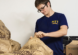 Patrick Callaghan, a volunteer from Pitt's Student Dietetic Association, inspects deliveries of potatoes.