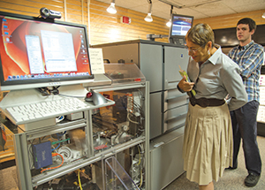 Pitt Professor Emerita of English Toi Derricote inspects the University Store's Espresso Book Machine, with print coordinator Greg Sciulli in background.