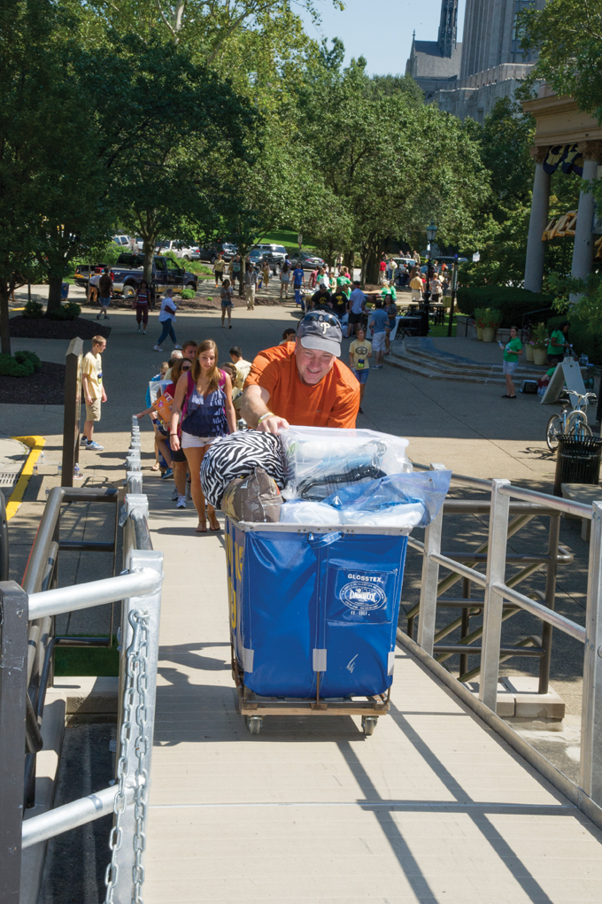 Parents and students make good use of Arrival Survival blue carts on move-in days. 6. Pitt Arrival Survival volunteers help families move boxes near Schenley Quad.
