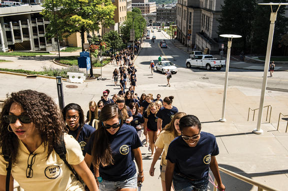 A steady stream of students walk up DeSoto Street toward the Petersen for convocation.