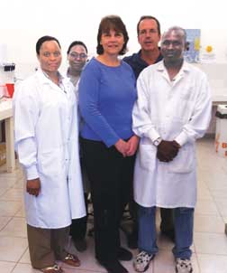Pitt researchers Deborah McMahon and Lee Harrison visit a laboratory supervisor and technicians in the Catholic University of Mozambique's (UCM) Infectious Diseases Research Center in Beira, Mozambique. McMahon (front row, center), a Pitt professor of medicine and of infectious diseases and microbiology, is the project director for Beira's Twinning Center, an HIV-focused health center where Pitt and UCM faculty train local health care workers in primary HIV care. Harrison, (back row, far right), a Pitt professor of medicine, epidemiology, and infectious diseases and microbiology, has helped train scores of Brazilian HIV researchers over the past 12 years. He and McMahon are discussing how U.S. and Brazilian researchers could train their Mozambique counterparts through an HIV research training program funded by the National Institutes of Health Fogarty International Center.