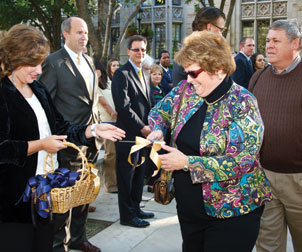 "Carol Simko Christobek (ENGR '77), an ODK awardee, receives her ribbon-cutting scissors for the ceremony. The ODK honor had been given exclusively to male seniors at Pitt for 52 years—becoming known as the ""Man of the Year"" award—until Christobek won it and received the certificate in 1977. But, alas, the finer text of the award certificate was left unchanged and refers to her ""as the senior man of the class of 1977."" Christobek said she still chuckles about the wording, adding that some things never change: When she attended last month's event with her husband, Mark Christobek (ENGR '77), some participants incorrectly assumed that he, not she, was the ODK alumnus."