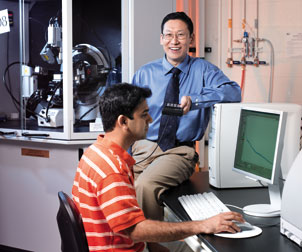 Part of the nanoscience research being done by Di Gao, a Pitt assistant professor of chemical and petroleum engineering and a W. K. Whiteford Faculty Fellow, is discovering how nanoparticles can be used to prevent ice buildup on road surfaces as well as on airplane wings and power lines. Here, Gao works with Ashish Yeri, a fourth-year PhD student. The large machine in the background is an X-ray diffractometer, which is used to examine the crystallinity of materials.