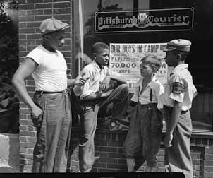 "Four paperboys stand outside The Pittsburgh Courier offices on Centre Avenue; photo by Charles ""Teenie"" Harris."