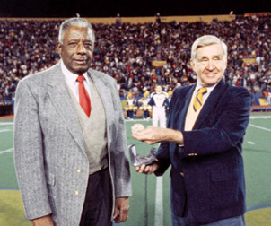 Pitt Chancellor Wesley W. Posvar presented John Woodruff with the University's Distinguished Graduate Medal award in 1982. Eight years later, Woodruff donated his 1936 Olympic Gold Medal to Pitt during the halftime of a 1990 Pitt-Notre Dame game in the old Pitt Stadium. Posvar received the medal on the University's behalf. Above, from left, Woodruff and Posvar.