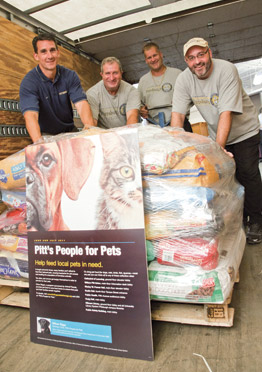 "Pitt's People for Pets campaign, held on the Pittsburgh campus during June and July, generated 4,000 pounds of donated pet food and nearly $2,000 in online cash donations—one of the largest and most successful such drives for Animal Friends' Chow Wagon program. Animal Friends operates the program to provide donated pet food to the region's food banks. ""The Chow Wagon program keeps pets in the home and tells the pet owners that people care about them,"" said Ann Cadman, health and wellness coordinator for Animal Friends. From left, Matt Sloan, Joe Healey, Dave Rahuba, and Dave Huey—all from Pitt's Department of Parking, Transportation, and Services' Central Receiving Office—load a pallet of donations for delivery to the Animal Friends shelter in Ohio Township. Officer Riggs, a Labrador Retriever and certified explosives detection specialist for the Pitt Police K-9 Unit, served as the Pitt campaign's honorary chair and spokesdog. Sponsors of Pitt's campaign were the Office of the Chancellor, the Office of Community Relations, the Department of Public Safety, and the University Library System."
