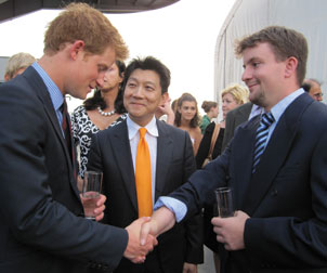 British Prince Harry (left) shakes hands with U.S. Marine Corporal Joshua Maloney (right), while W.P. Andrew Lee looks on. Lee, a professor of surgery and orthopedic surgery as well as chief of the Division of Plastic Surgery in the University of Pittsburgh School of Medicine, performed the 2009 transplant that gave Maloney a new right hand. Maloney's own hand had been destroyed during a 2007 military training exercise. The three men met in New York City during a June 25 reception that Prince Harry hosted on the aircraft carrier USS Intrepid to honor British and American veterans. The prince, who is training to become a pilot with the British Army Air Corps, is interested in Pitt and UPMC's hand-transplantation program. He spoke with Lee and Maloney about the medical procedure and its potential to help other wounded warriors.