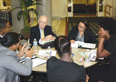 J. Roger Glunt (center), an emeritus trustee on Pitt's Board of Trustees, works with a group of students during the Hesselbein Academy Summit. Glunt was one of nine professional mentors who delivered presentations on various leadership topics and worked personally with students during the four-day summit.