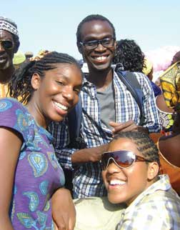 "Pitt senior Sesi Aliu (center) on a ferry in The Gambia crossing the nation's namesake river from the city of Barra to the capital of Banjul. Joining him were ""hundreds of people, livestock, food, cars, and other goods."""