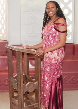 Yolanda Covington-Ward stands in the Cathedral of Learning's African Heritage Nationality Room. She is wearing a skirt and top made out of fabric given to her by a Nigerian friend. The type of fabric used is popular throughout West Africa and is often worn to such events as weddings or formal dances.