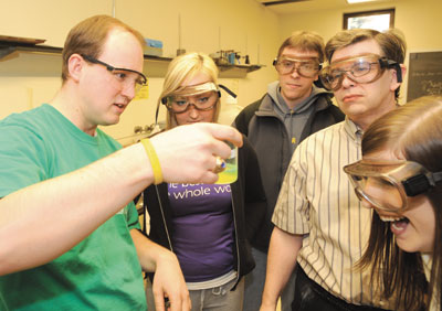 Peter Bell, a Pitt doctoral student in chemistry, conducts an experiment for his organic chemistry class, while George Bandik, a senior lecturer and director of undergraduate studies for Pitt's Department of Chemistry, looks on. From left are Bell, sophomore Vanessa Cole, junior Jason Zlotnicki, Bandik, and sophomore Kaitlyn Musco.