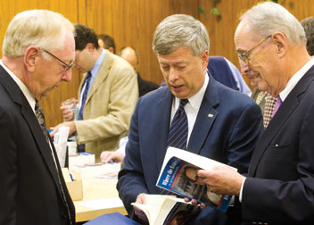 From left, University Library System (ULS) Director Rush Miller, Pitt Chancellor Mark A. Nordenberg, and Dick Thornburg inspect Thornburgh's book, Where the Evidence Leads, which was printed in about seven minutes from a digital file.