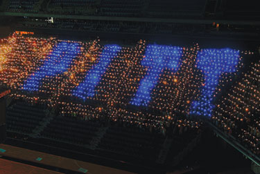 "Forming the word P-I-T-T with blue flashlights, 2,496 new students gathered Aug. 26 in the Petersen Events Center in an attempt to break the Guinness World Record for the ""World's Largest Torchlight (Flashlight) Logo/Image Formed by People."""