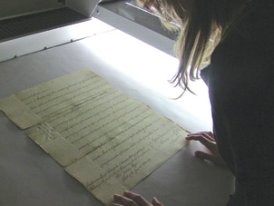 University Library System Associate Katrina Milbrodt scanning a page of the 1787 charter.