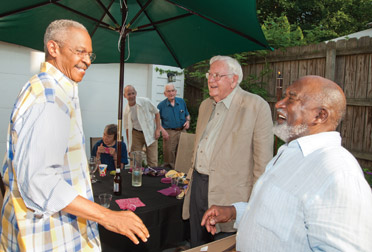 "CELEBRATING WITH THADDEUS MOSLEY:  Friends and families celebrated Thaddeus Mosley's (A&S '50) ""near 85 years of energetic life"" during a June 11 outdoor party at the Highland Park home of Terry Seya (KGSB '93). Mosley (far right) is a prominent and nationally known sculptor, based in Pittsburgh, who works primarily in wood. He is talking with Davis Lewis (center, front), an architect, writer, painter, and longtime friend, and Robert Hill (far left), Pitt's vice chancellor for public affairs. Lewis is the author of Thaddeus Mosley: African-American Sculptor (University of Pittsburgh Press, 1997)."