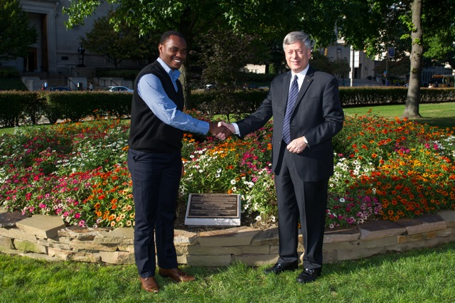 Nicholas Wambua, a Pitt School of Law student and Kenyan native, shakes hands with Chancellor Nordenberg at the dedication of the Wangari Maathai Trees and Garden.